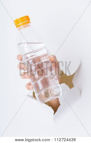 Woman hand with bottle of water through a hole in paper