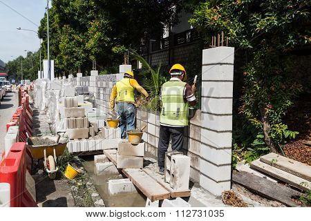 Workers Constructing Building Noise Barrier Walls At Busy Highway