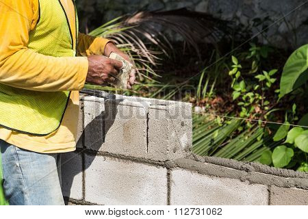Worker Inserting Noise Proofing Sponge Into Barrier Bricks During Construction