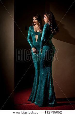 Elegant young woman in turquoise long dress looking into a large mirror, side view