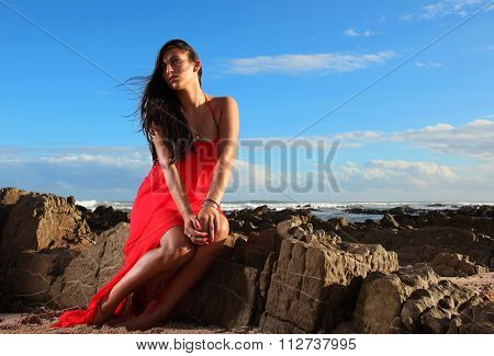 Brunette In Red Dress On The Beach