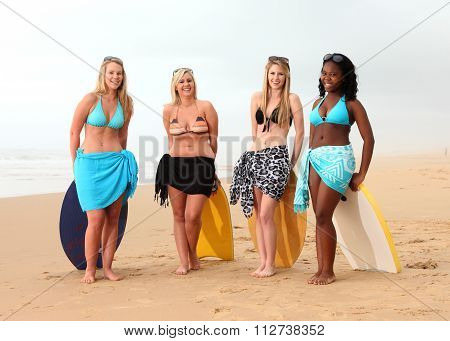 Four Girl Friends Resting On Surf Boards