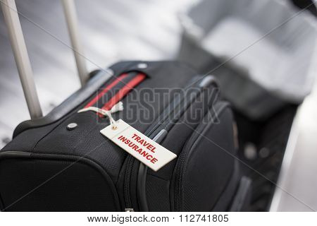 Travel insurance concept, travel insurance label tied to a suitcase
