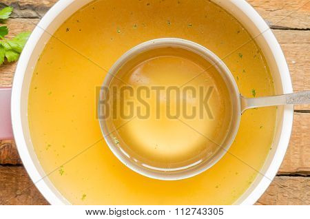 Spoon With Bouillon To The Pan With Bouillon Background