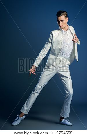 Full length portrait of a handsome young man in white suit in motion. Secret agent.