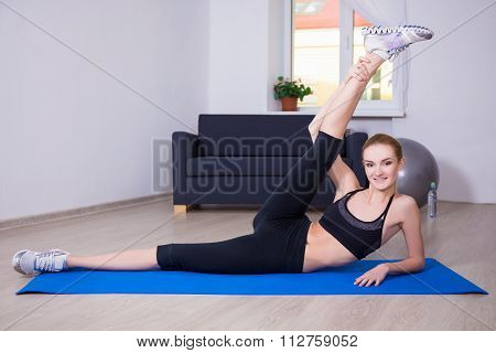 Healthy Lifestyle Concept - Slim Flexible Woman Doing Stretching Exercise On Yoga Mat