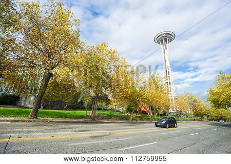 Seattle, USA-Nov, 6, 2015: landmark Space Needle stands by rural road through forest in cloudy sky