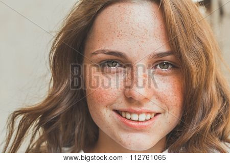 Outdoor Beauty. Portrait Of Smiling Young And Happy Woman With Freckles.