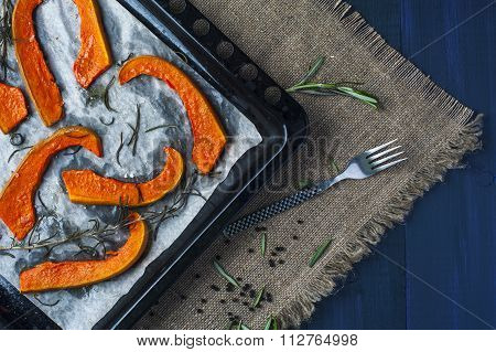 Slices of baked pumpkin on baking tray