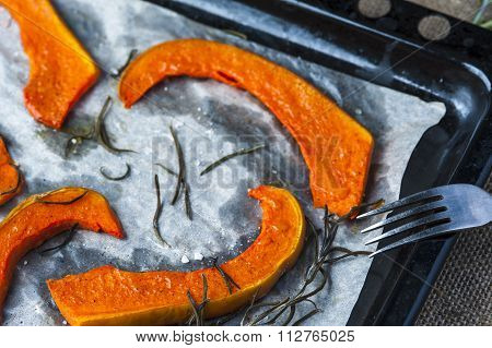 Slices of baked pumpkin on baking tray with fork