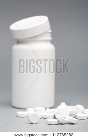 Round white tablet with the pill bottle