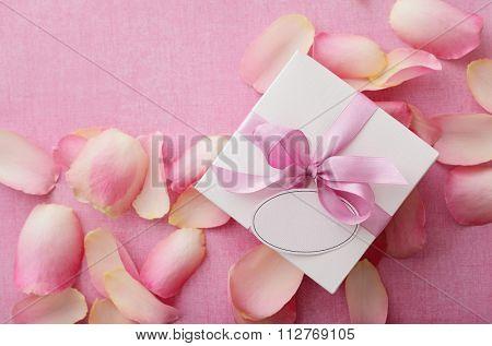 gift box with pink ribbon bow and rose petals