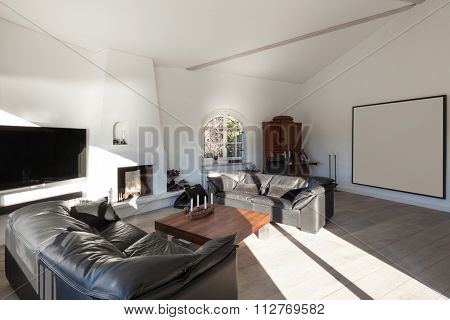Interior of house, comfortable living room with leather divans