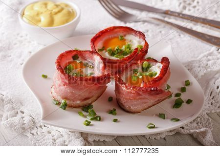 Fried Eggs Wrapped In Bacon On A Plate And Sauce. Horizontal