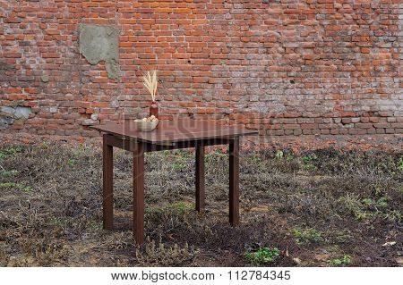 Woden Table With Vase And Wallnuts Standing On The Ground Near Old Brick Wall