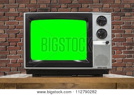 Analog television with brick wall and chroma key green screen.