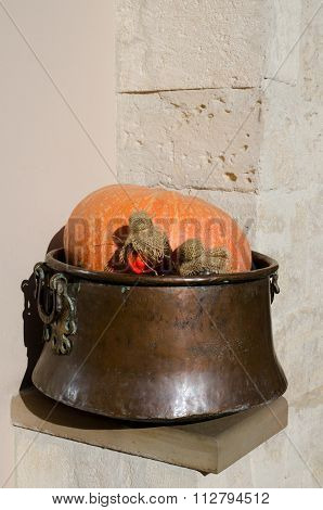 Pumpkin With Bottles Of Potions In A Copper Vat On Wall Background. Vertical View
