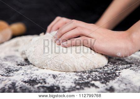 Baking preparing background. Female hands knead dough on the worktop.