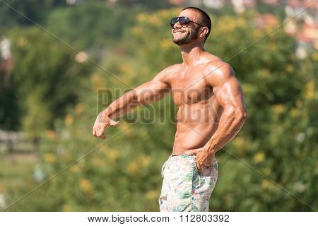 Man Flexing Muscles Outdoors In Summer Time