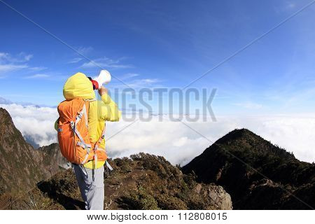 young woman backpacker  shout with loudspeaker on mountain peak