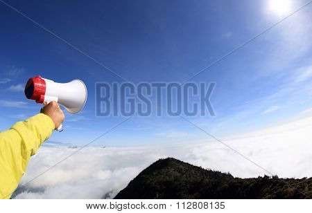young woman hand shout with loudspeaker on mountain peak