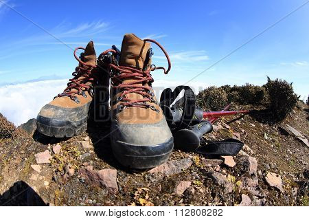 pair of hiking boots and hiking pole on mountain peak