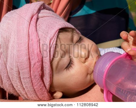 Baby Girl Eating Milk From Bottle