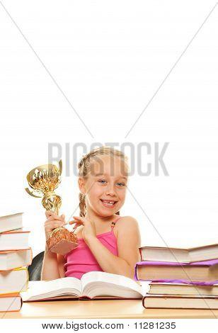 Happy little schoolgirl with a golden cup