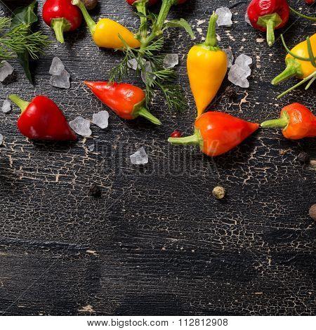 Top Down Of Yellow, Orange And Red Hot Chili Peppers, Sea Salt, Greenery, Black Pepper On Cracks Bla