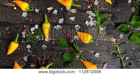 Top View Of Yellow Hot Chili Peppers, Sea Salt, Greenery On Cracks Black Background, Panorama