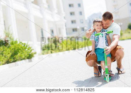 Father teaching son to ride a scooter