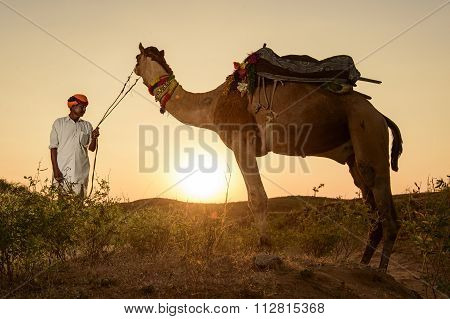 Camel Trader crossing the sand dune during sunset at sunset point.
