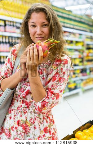 Young woman stands in a supermarket with Pitaya (dragon fruit) in his hands.