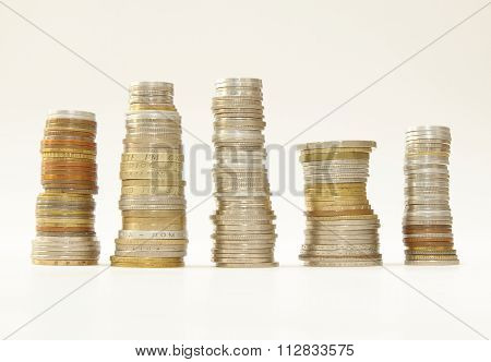 Stakes of diverse coins on white background