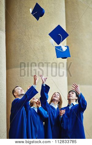 Group of happy graduates throwing their mortarboards upwards