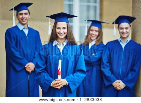 Pretty students in graduation gowns and mortarboards