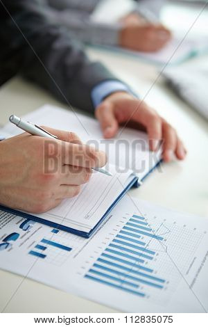 Male hand making notes in notebook with document near by