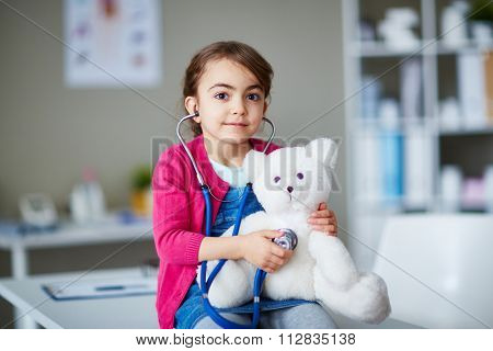 Little clinician examining her teddybear