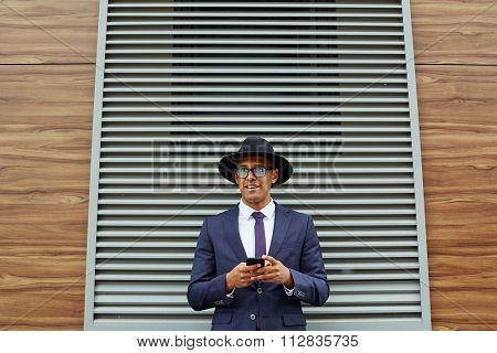Elegant businessman with cellphone standing against jalousie