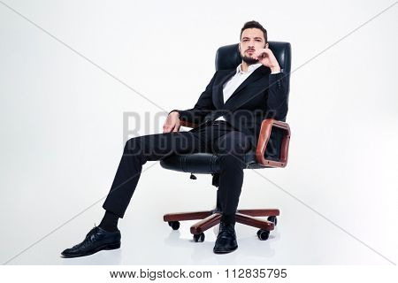 Full lenght of assured confident young business man with beard in black suit sitting in office chair and looking camera over white background