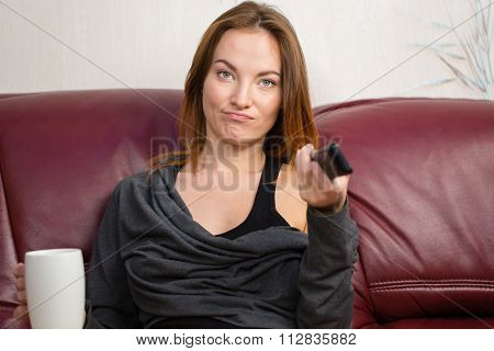 Annoyed beautiful young woman drinking tea and using tv remote control on couch in living room