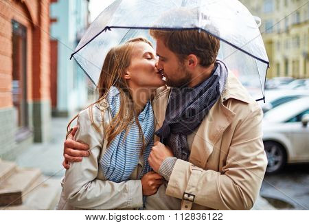 Amorous young couple sharing tender kiss under umbrella