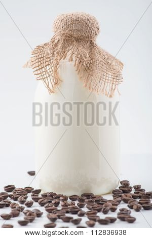 Glass bottleful of milk and coffee beans.