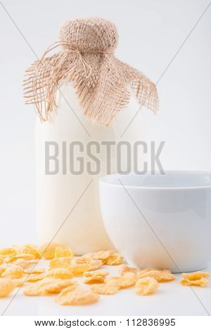 Bottle of milk, corn flakes and bowl.