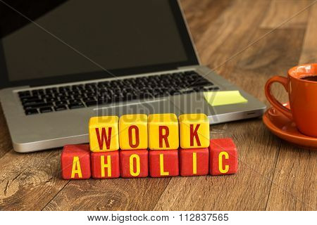 Workaholic written on a wooden cube in a office desk