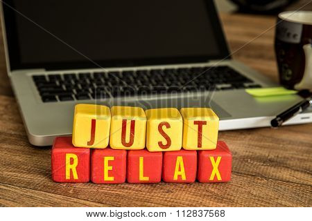 Just Relax written on a wooden cube in a office desk