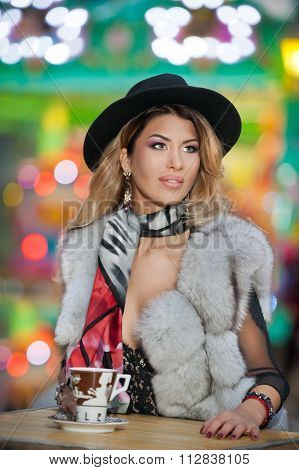 Long fair hair young beautiful woman with black hat, scarf and fur coat, outdoor shot