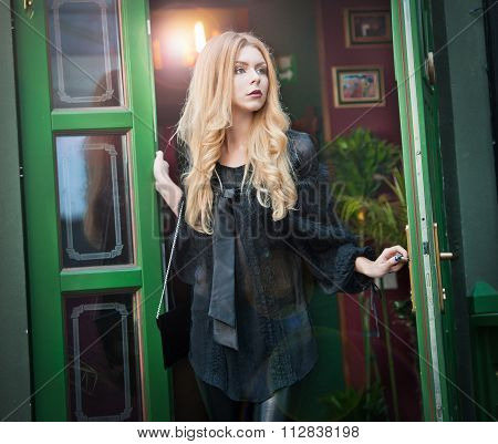 Charming young blonde woman in black outfit posing in a green painted door frame. Sexy gorgeous girl