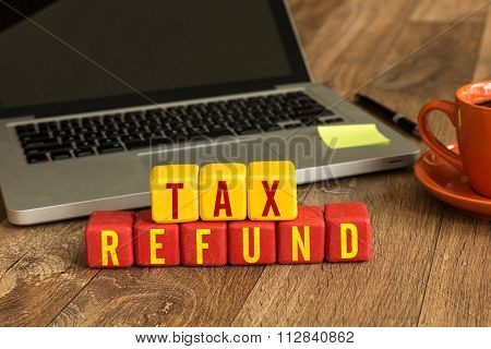 Tax Refund written on a wooden cube in a office desk