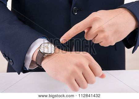 Man pointing at the wristwatch.